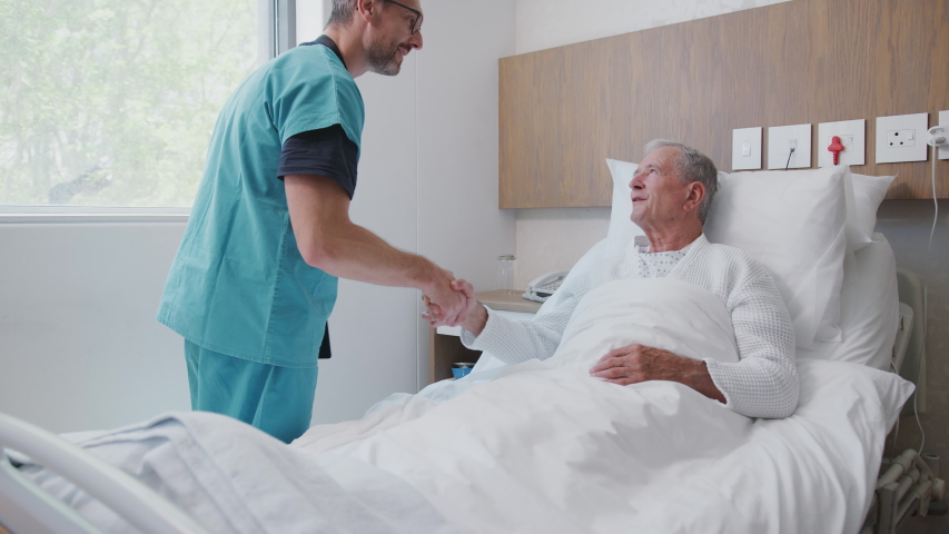 Surgeon Visiting And Shaking Hands With Senior Male Patient In Hospital Bed In Geriatric Unit