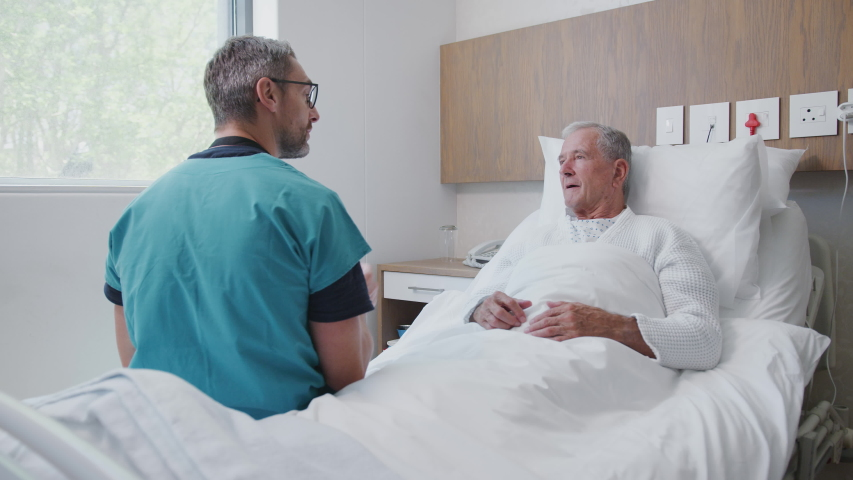 Surgeon Visiting And Talking With Senior Male Patient In Hospital Bed In Geriatric Unit