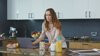 Business woman preparing breakfast in a hurry in luxury kitchen. Busy mother running to work. Multitasking woman making food in a rush in private house.