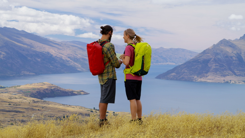 Young Caucasian male and female enjoying hike having fun reading map of Fjordland The Remarkables New Zealand RED WEAPON | Shutterstock HD Video #1031132081