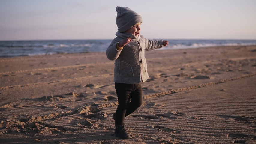 Happy little toddler running to her mother hugging on the autumn beach. Cute kid hugging his mom and they falling down on the sand. Concept mom with a child outdoors, happy family, Happy Childhood