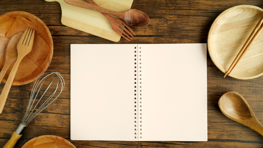 A male hand open recipe cooking book  paper 3 page  with cooking equipment on the wooden desk, top view and overhead shot use for blank template book mock up to add any text content for cuisine cookin