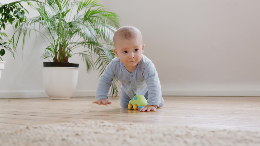 Curious Baby Boy Playing With Toys On Floor At Home Crawls Towards And Looks At Camera | Shutterstock HD Video #1031167922