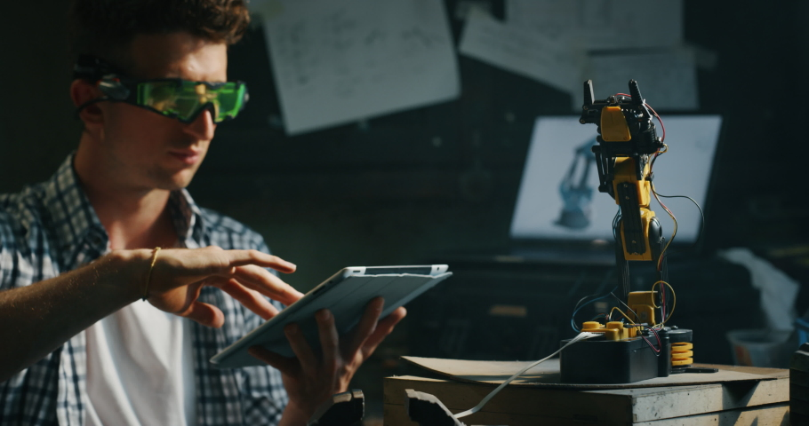 Slow motion of an young professional engineer with specific glasses is using a tablet for working on projection of an innovative technology mechanical arm  in his workshop. | Shutterstock HD Video #1031174372