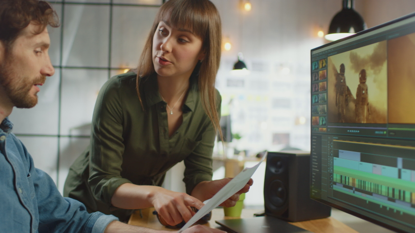 Beautiful Female Art Director Consults Handsome Video Editor Colleague, They Work on a Video Project About Astronauts. They Work in a Cool Office Loft. They Look Very Creative and Cool. | Shutterstock HD Video #1031177417
