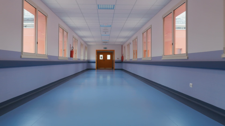 Long empty corridor of a large building, towards the exit. Passage through a long empty corridor to exit direction. First person view