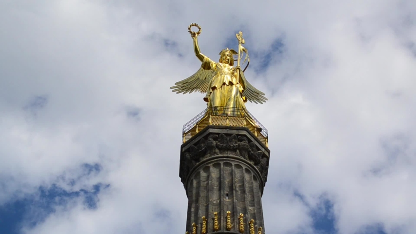 Siegessaule or Victory column with golden statue in Berlin, Germany. Time lapse of clouds passing behind monument. Major tourist spot and sight in city. Famous landmark and popular tourist attraction.