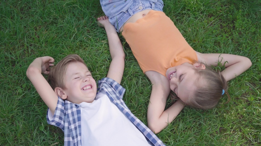 Two funny kids lying on the grass in the park smiling to each other. The girl taking hand of the boy. A couple of happy children. Funny carefree kids in love. Top view