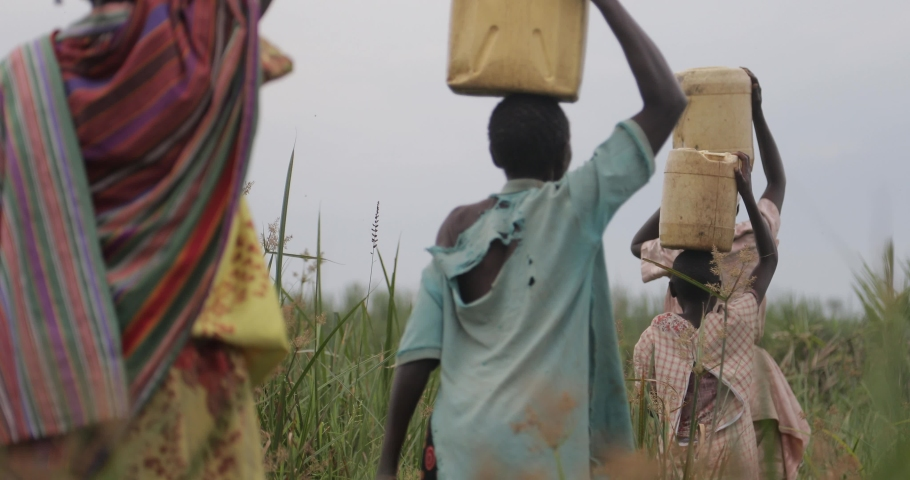 A group of women and girls carrying water in yellow jerrycans on their heads Mbale, Uganda South Africa