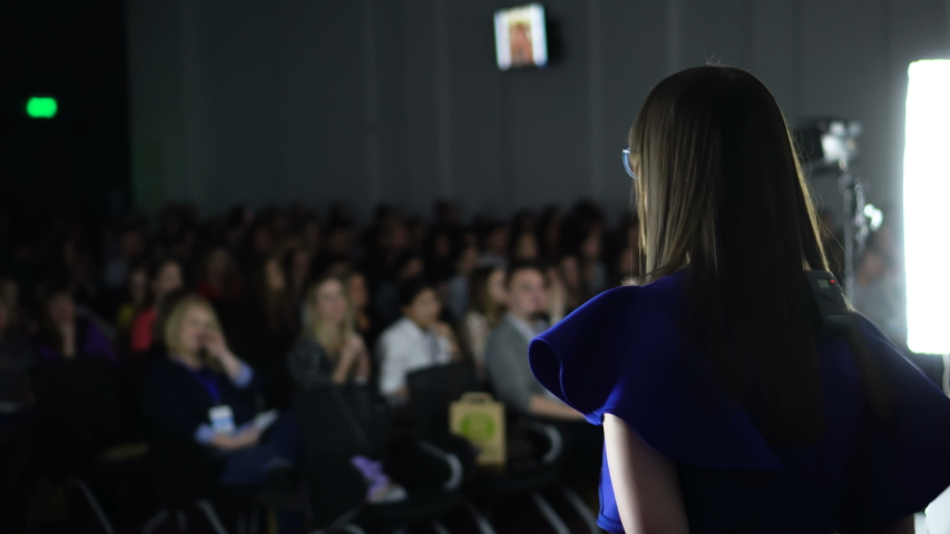 Female Speaker giving Presentation in Lecture Hall. Young Woman Talking to People. Rear View of Unrecognized Participant in Audience. Scientific Conference Event Footage Shot in 4K #1031219708