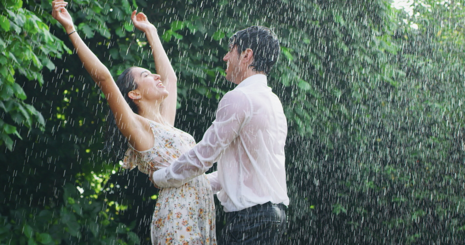 Slow motion of young carefree couple in love are dancing and kissing under the rain on a background of green trees.