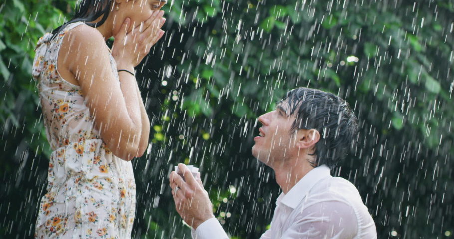 Slow motion of young handsome man is making a proposal of marriage to his fiancee under the rain on a background of green trees.
