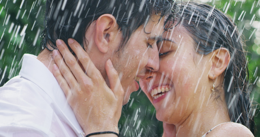 Slow motion of young carefree couple in love are hugging and kissing under the rain on a background of green trees.