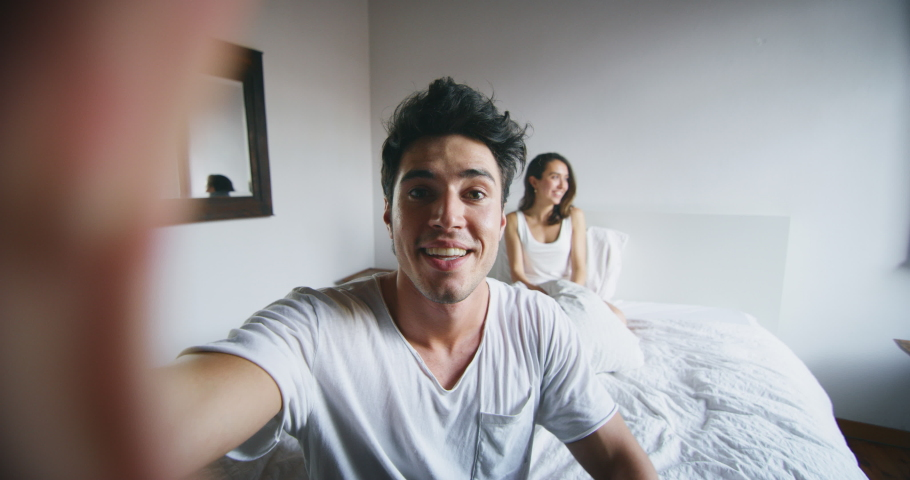Authentic shot of young just married couple are making a selfie or video call to relatives or friends with smartphone in the bedroom in the early morning in a sunny day. | Shutterstock HD Video #1031238551