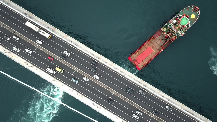Top down view of car traffic on the bridge across the sea. Aerial. Towing convoy consisting multiple tow boats passing under the Bosphorus Bridge