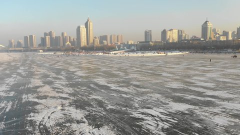Drone shot of frozen Songhua river and skyline of Harbin in cold Winter weather China