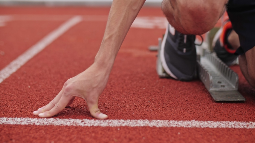 Unrecognizable Male Athlete Preparing For Running Track. Track Runner Putting  His Hands At Starting Line. 4k . SLOW MOTION | Shutterstock HD Video #1031263052