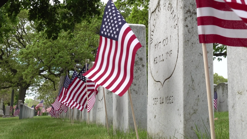 Close up side view of gravestones in a cemetery of civil war soldiers remains on Memorial day with American flags flapping in the wind