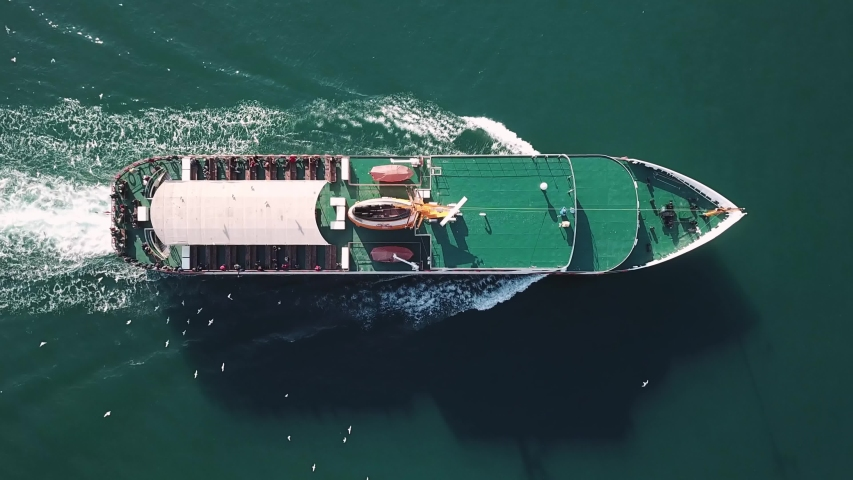 A classic Istanbul ferry underway with the seagulls. Aerial birds eye view of a ferryboat traveling in the Bosphorus Sea. Leaves a wake behind it. Smooth glassy water. Top down, tracking shot  | Shutterstock HD Video #1031273093
