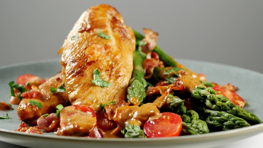 Roasted chicken breast, served on asparagus with tomato sauce, dried tomatoes. Front view. Presentation of the dish. Rotating and moving the camera. Adding ingredients, decoration.