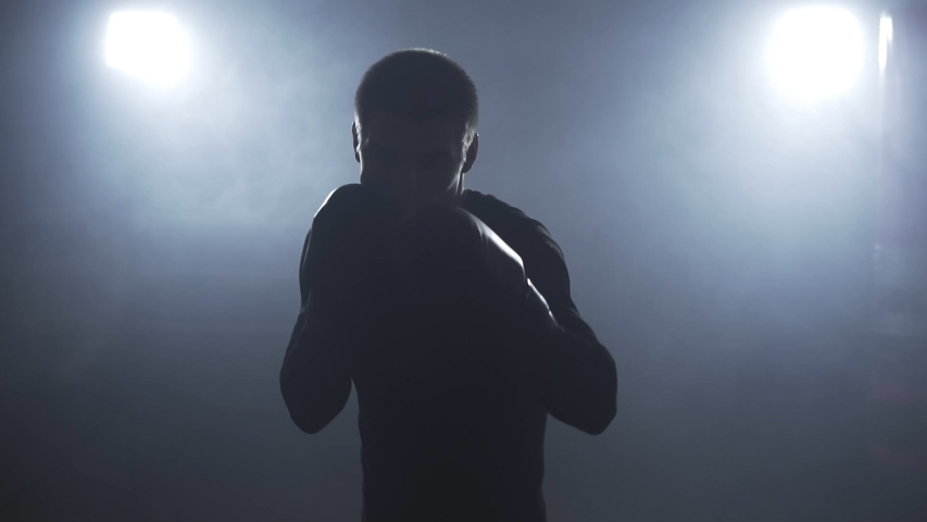 Kickboxer training in low light gym. Sportsman boxing in camera. Muay thai fighter punching. Silhouette on dark background. Medium shot with camera shaking when boxer punching | Shutterstock HD Video #1031299259