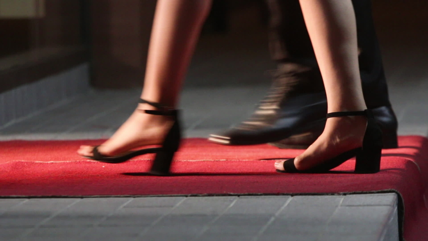 Celebrities walk the red carpet. Movie stars arrive for a premier. Low angle view of people arriving at a formal event and walking a red carpet as they enter. Women in heels and dresses. Royalty-Free Stock Footage #1031305385