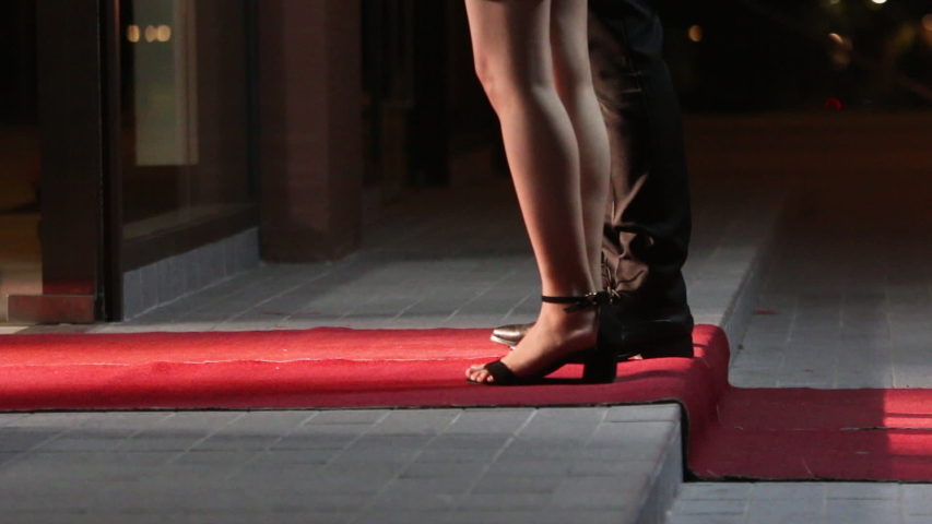 Low angle view of people arriving at a formal event and walking a red carpet as they enter. Women in heels and dresses. Celebrities walk the red carpet. Movie stars arrive for a premier. #1031305400
