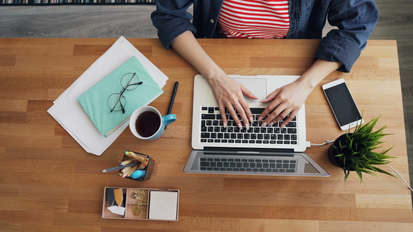 Zoom-in top view of young woman using laptop typing in office at wooden desk working alone. Personal things are visible on table - coffee cup, notebook, plant. Royalty-Free Stock Footage #1031320733