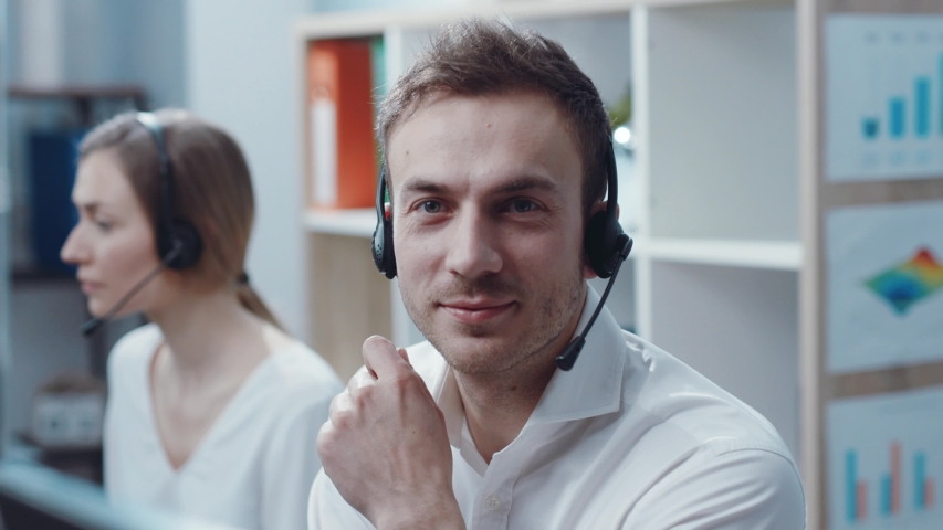 Face young handsome man operator look at camera smie taking calls smile in call center office business worker computer corporate headset job service group finance sunshine phone close up slow motion