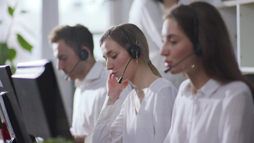 Portrait young people operator taking calls smile in call center office business worker computer corporate headset job man service group finance sunshine phone close up slow motion