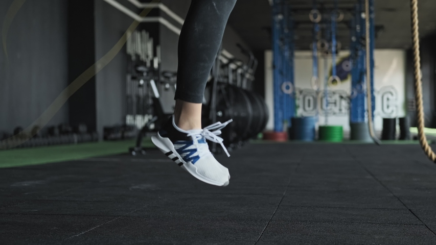 Close-up of woman's legs in sport black outfit jumps the rope in gym. Athletic woman exercises with skipping rope indoors. Female performing skipping rope workout. White shoes. Side view