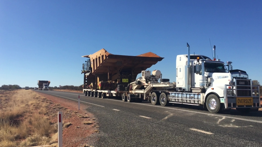 ALICE SPRINGS,NT-MAY 15 2019:Oversize vehicle convoy on Stuart highway in the red center of Australia outback.Load shifting in the responsibility of the shipper, motor carrier, driver and the receiver