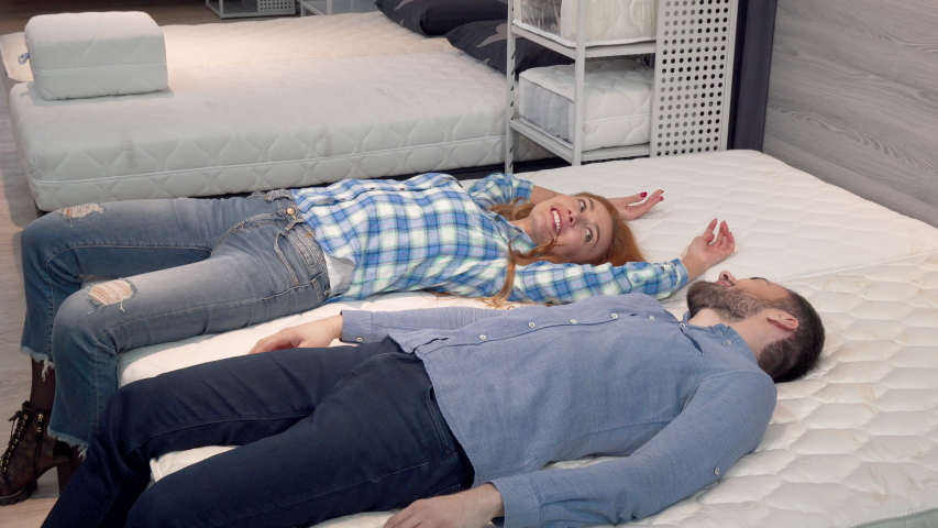 Lovely happy couple lying on comfortable othopedic mattress at furniture shop #1031377370