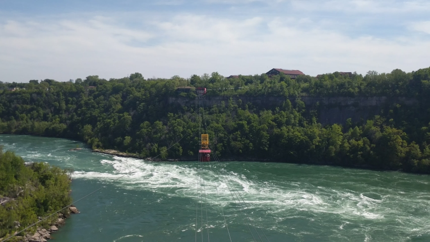4K footage of a red cable car on sturdy metal cables moving over a green emerald water of Niagara River Whirlpool. One of the major attractions at Niagara Falls, Canada. Sunny summer day.