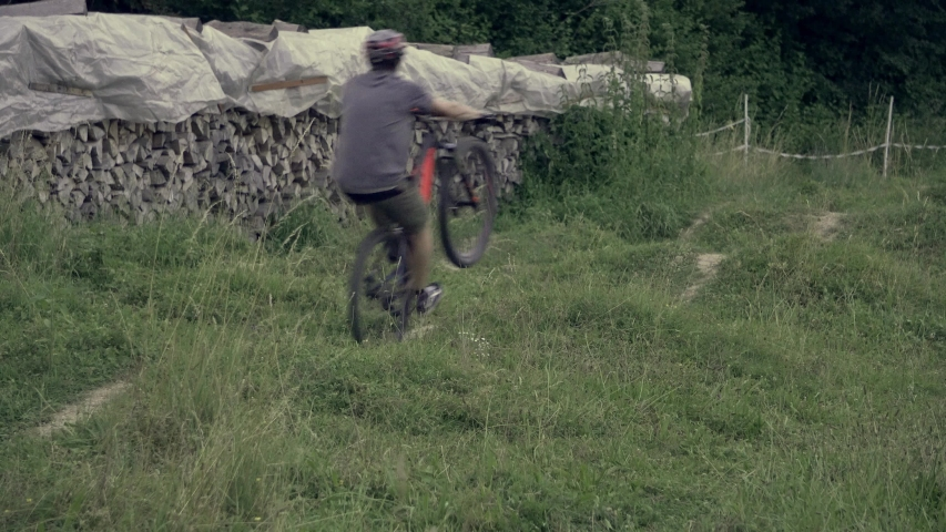 Mountainbiker rides a pumptrack and does a manual trick. 4K.