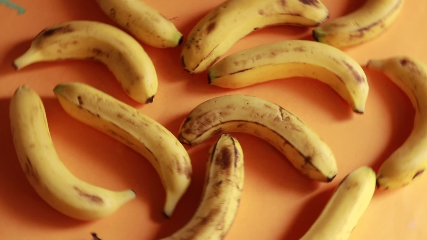 Ripe delicious wet bananas rotate clockwise on a black plate on a yellow background | Shutterstock HD Video #1031417051