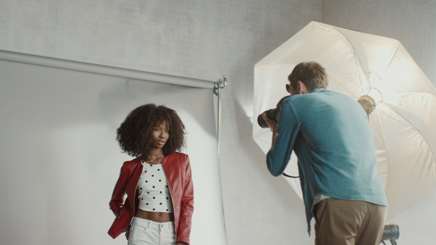 Backstage of the Photo Shoot: Make-up Artist Applies Makeup on Beautiful Black Model, in a Moment Photographer Starts Taking Photos with Professional Camera. Fashion Magazine Studio Photoshoot