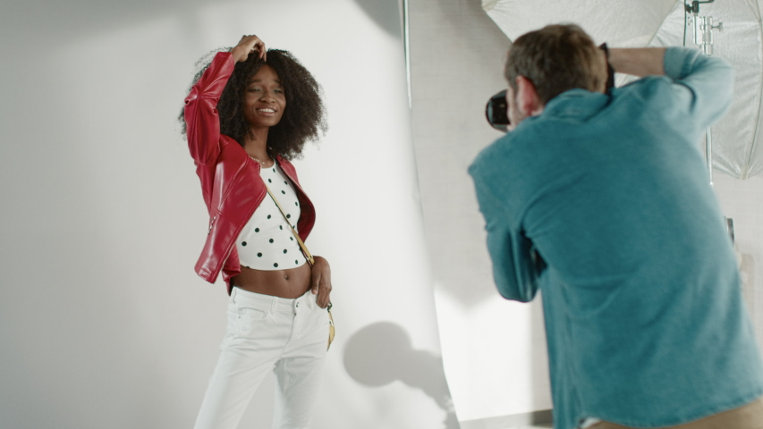 Behind the Scenes on Photo Shoot: Beautiful Black Model Posing for a Photographer, he Takes Photos with Professional Camera. Stylish Fashion Magazine Photoshoot done with Pro Equipment in a Studio Royalty-Free Stock Footage #1031450312