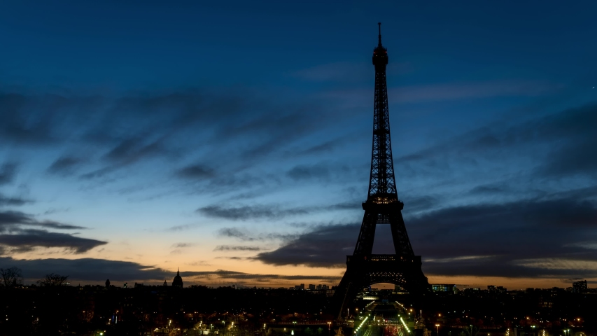 Night to Day timelapse of Eiffel tower in winter from Trocadero on a cloudy day - Paris, France.