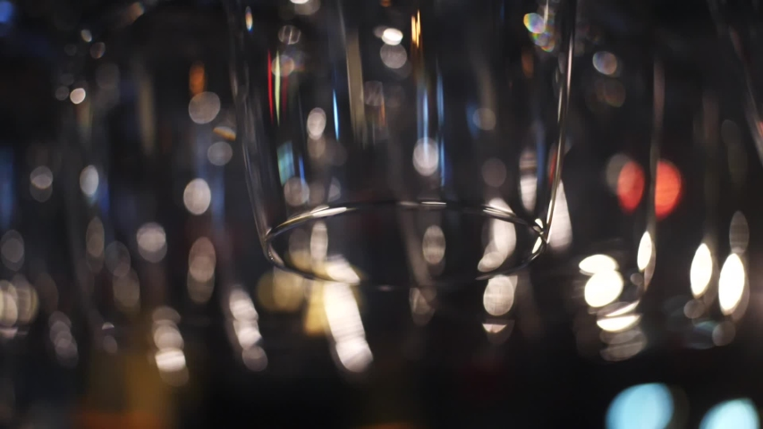 Empty glasses for wine and other alcoholic drinks hanging over the bar counter. Frame. Blurred view of wine glasses | Shutterstock HD Video #1031460449