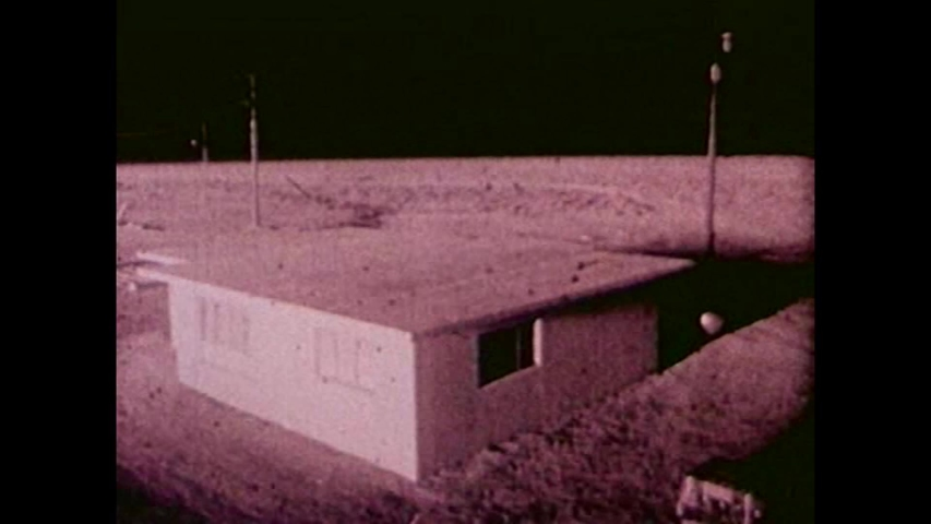 CIRCA 1950s - A model village is blown away by a nuclear bomb blast in the Nevada desert.