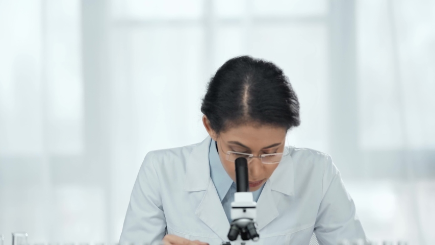 African american scientist in glasses using microscope and then looking at camera | Shutterstock HD Video #1031497124