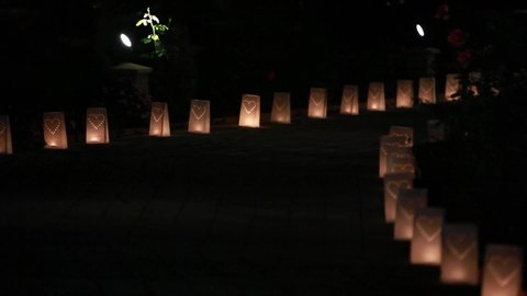 Paper bag lanterns on stairs. Candle light. Pierced in a heart shape. Romantic decoration