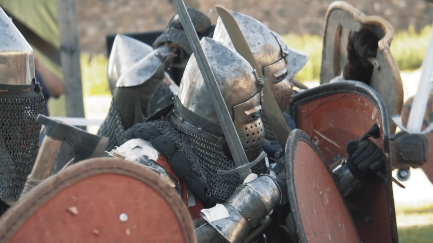 Medieval knight battle. Warriors in full plate armor with melee weapons. Armed men fighting. Real historical warfare reenactment | Shutterstock HD Video #1031516750