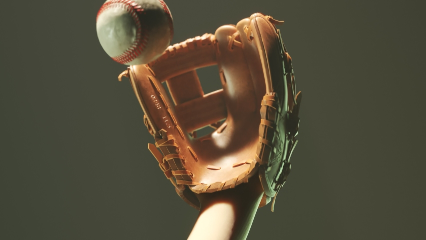 Dynamic baseball catch in the spotlight. Epic foggy slow motion shot of ball flying towards the glove. Dust particles appearing as the ball losing its momentum in the glove. 4KHD