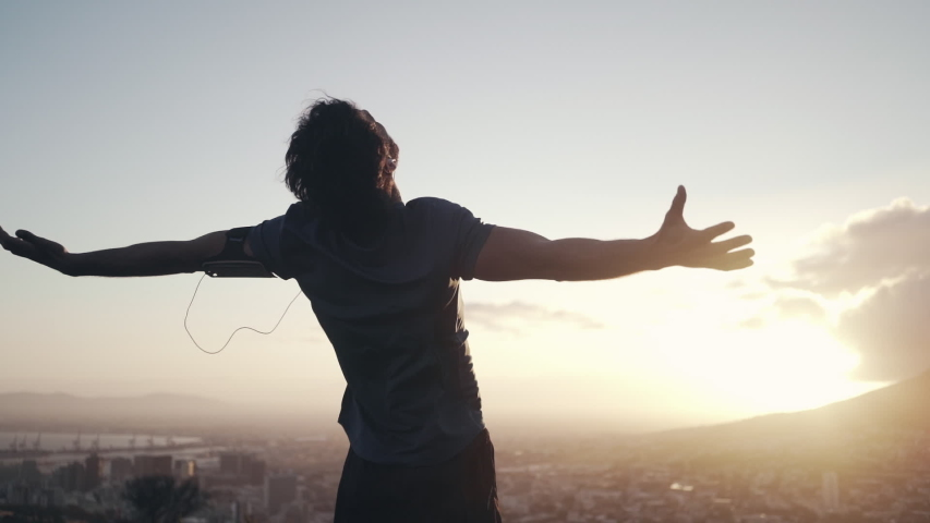 Male athlete out stretching his hands against sunrise