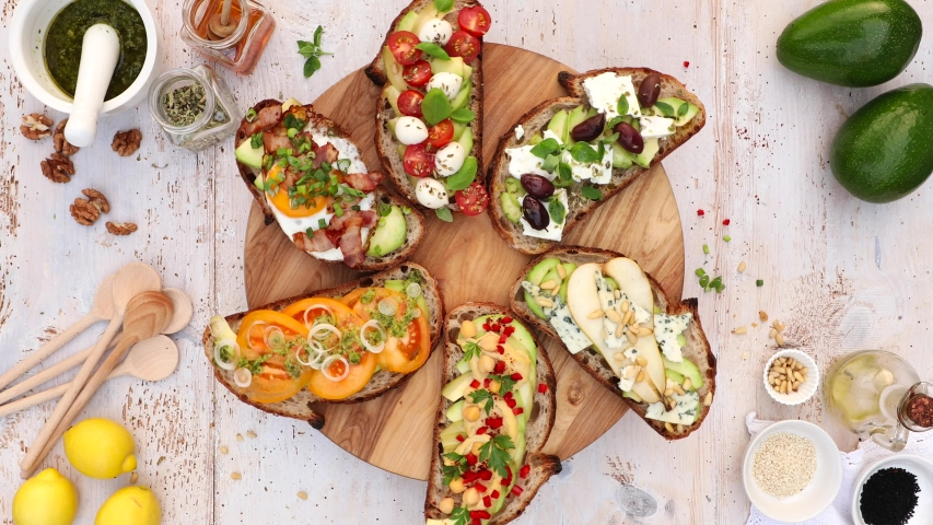 Assorted  open faced sandwiches, Open avocado sandwiches made of  slices of sourdough bread with  various toppings on a round board, on a white wooden table, top view, 4k. #1031552876
