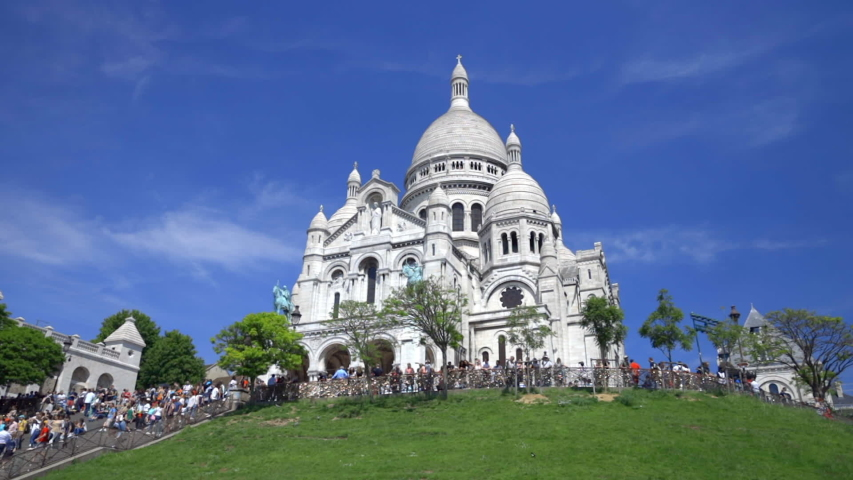 Paris, France - June 2019 : Basilica of the Sacré-Coeur, the Sacred Heart, the famous church in Montmartre in Paris France on a spring day with a blue sky with tourists climbing the stairs of the hill