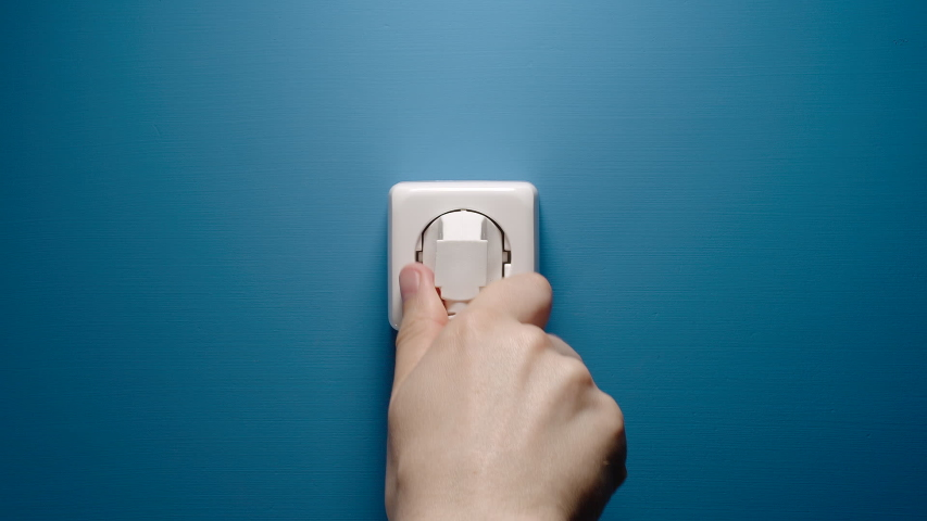 Man Inserts Plug Into Electrical Socket On A Blue Wall