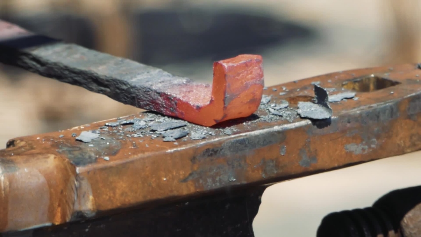 Smith forming red hot iron in hook on anvil. Blacksmith in forge beats hammer hot metal on anvil. Smithy  on the street. Slow motion, close up.